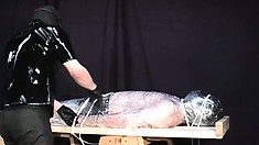 Master dressed in all black, with a hood, covers his gay slave in plastic wrap